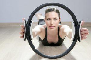 magic pilates ring woman aerobics sport gym exercises on wooden floor